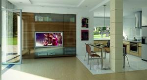 Jasne wnętrze domu z interesującymi drewnianymi akcentami jest kontynuacją charakteru elewacji – białego tynku uzupełnionego drewnem.