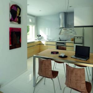 Białą kuchnię uzupełniono metalicznymi okuciami wkomponowanymi w jasno drewniane fronty meblowe. Fot. Biuro Projektów MTM
