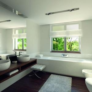 Biała glazura i ceramika sanitarna idealnie komponuje się z ciemnobrązowymi szafkami i parkietem w podobnym odcieniu. Fot. Biuro Projektów MTM