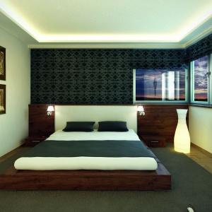 W sypialni biel wnętrza uzupełniono ciemną tapetą i roletami oraz brązowymi meblami. Fot. Biuro Projektów MTM
