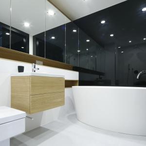 Minimalistyczny wystrój łazienki zdominowany przez nowoczesne formy wyposażenia oraz achromatyczne barwy ociepla fornirem jasnego dębu. Fot. Bartosz Jarosz