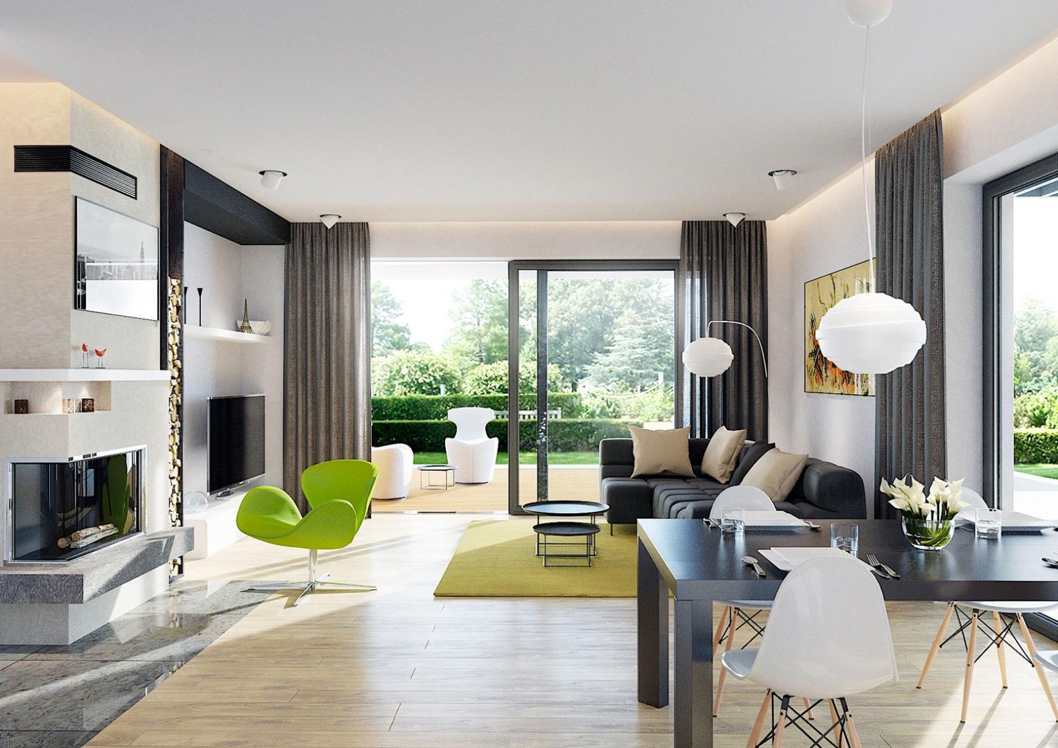 Wnętrze domu to dużo przestrzeni, bieli i światła. Królują tu szerokie przeszklenia, dzięki którym granica między salonem a ogrodem praktycznie się zaciera. Uwagę zwraca dekoracyjny kominek ikona designu – fotel Swan w kolorze soczystej, energetycznej zieleni. Fot. Pracownia Projektowa Archipelag