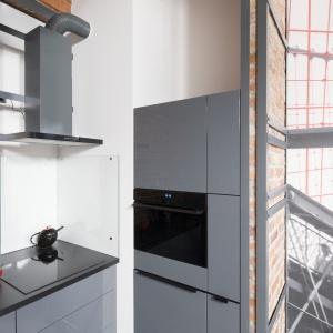 Kolorystyka mebli kuchennych naturalnie nawiązuje do stylistyki panującej w strefie dziennej. Fot. Bartosz Jarosz
