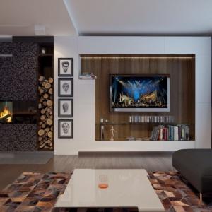 Narożny kominek zaplanowany na granicy salonu z holem i jadalnią pozwala podziwiać płonący w nim ogień z perspektywy każdej części pomieszczenia. Proj. Nowik, Fot. Archetyp