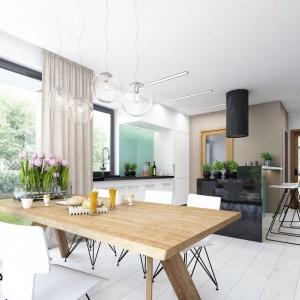 """Centralnym punktem jadalni jest piękny drewniany stół w jesionowym odcieniu. Okalają go nowoczesne, białe krzesła o """"lekkiej"""" konstrukcji. Ważnym elementem dekoracji tej przestrzeni są lampy nad stołem. Projekt: Tris II, Fot. Dobre Domy"""