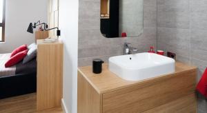 Łazienka o hotelowym charakterze została zaprojektowana z myślą o oszczędności miejsca. Mały metraż wymagał jasnych okładzin ścian, podwieszanej ceramiki czy montażu niedużej, lecz pojemnej szafki podumywalkowej.