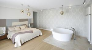 Sypialnia połączona z łazienką to rozwiązanie wybierane przez coraz większą liczbę inwestorów. Połączenie tych dwóch przestrzeni pozwala zrezygnować z tradycyjnych ścianek działowych, co z kolei pozwala na powiększenie przestrzeni zarówno