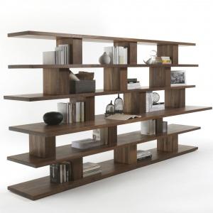 Drewniany regał na książki BOOKSHELVES składa się z półek o różnych głębokościach ułożonych asymetrycznie, w efekcie środkowa półka może pełnić rolę biurka. Ażurowa konstrukcja pozwala przedzielić pomieszczenie. Fot. Riva 1920/ Kari Mobili
