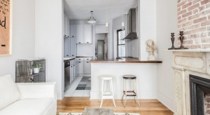 Gdybyśmy mieli określić charakter tego wnętrza jedynie na podstawie jego kolorystyki, uznane zostałoby za skromne i neutralne. Panują tutaj bowiem szarości i biel, z cieplejszymi akcentami w postaci drewna czy czerwonej cegły.