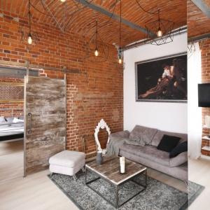 Jedną ze ścian w loftowym salonie zdobi duże, pionowe listro, które optycznie powiększa przestrzeń niewielkiego mieszkania. Projekt: Tomasz Jasiński. Fot. Bartosz Jarosz