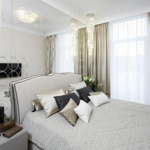 Bardzo elegancka, stylowa sypialnia. Ciekawym elementem jest lustro zajmujące całą ścianę za łóżkiem. Projekt: Karolina Łuczyńska. Fot. Bartosz Jarosz