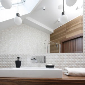 Białe płytki ceramiczne i ogromne lustro optycznie powiększa przestrzeń łazienki na poddaszu. Projekt: Jan Sikora. Fot. Bartosz Jarosz
