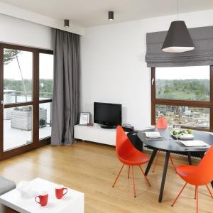 Jadalnia znajduje się w otwartej strefie dziennej. Charkteru dodają jej czerwona krzesła o fajnym kształcie. Projekt: Małgorzata Łyszczarz. Fot. Bartosz Jarosz