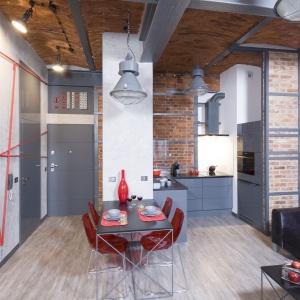 Jadalnię umiejscowiono w salonie. Stół o lekkiej konstrukcji doskonale wpisuje się w klimat wnętrza, podobnie jak nowoczesne, czerwone krzesła z plexi. Projekt: Małgorzata Chabzda. Fot. Bartosz Jarosz