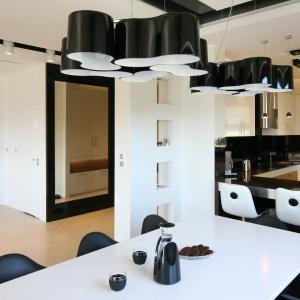 Pomiędzy salonem a kuchnią ustawiono duży, rodzinny stół. Dzieli on obie przestrzenie, a jednocześnie do spółki z wysokim, ceglanym barkiem lekko osłania kuchnię przed strefą wypoczynkową. Fot. Bartosz Jarosz.