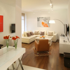Biały salon ożywiono ciemnobrązową drewnianą podłogą i pomarańczowymi oraz czerwonymi obrazami na ścianach. Projekt: Małgorzata Galewska, Fot. Bartosz Jarosz