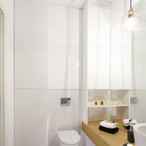 Ścianę nad WC wykorzystano bardzo praktycznie. Białe, gładkie fronty skrywają pojemne szafki. Projekt: Ola Kołodziej, Ula Szmyt. Fot. Bartosz Jarosz