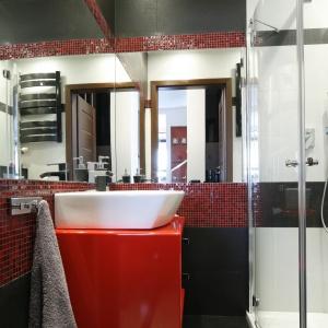 Bardzo mała łazienka z prysznicem. Mimo ciemnych kolorów wnętrze nie sprawia wrażenia mniejszego niż jest w rzeczywistości. To zasługa dużych luster oraz czerownych akcentów. Projekt: Marta Kilan. Fot. Bartosz Jarosz