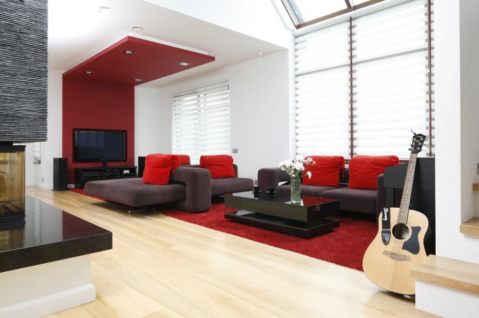 Jeśli decydujemy się na wprowadzenie intensywnego koloru - to warto w tym odcieniu pomalować tylko fragment ściany. Salon ożywiły również soczystoczerwone poduchy i dywan. Projekt: Michał Mikołajczak, Fot. Bartosz Jarosz