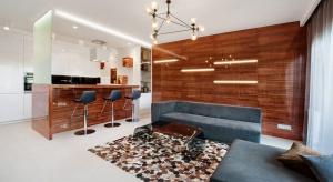 Jasny i przestronny, a przy tym w 100% nowoczesny. W tym apartamencie kontrast dla jasnych powierzchni stanowią ciemne meble ofakturze drewna, w połysku.