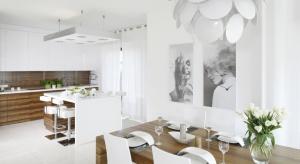 Ciepła i przytulna kuchnia może być utrzymana w nowoczesnym stylu. Wystarczy sięgnąć po drewno, by nawet białej zabudowie meblowej nadać domowy charakter.