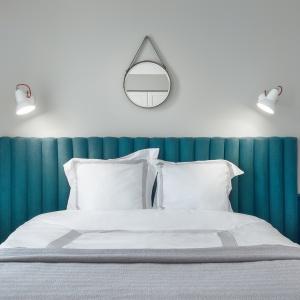 Po obu stronach łóżka ustawiono dwa stoliki w stylu skandynawskim, a nad zagłówkiem zawieszono lustro i kinkiety  marki Anglepoise. Fot. JTgrupa
