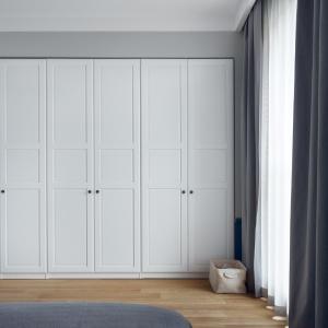 Mocny kolor obicia przełamują jasne ściany oraz szara narzuta i zasłony. Naprzeciwko łóżka znajduje się imponująca garderoba zabudowana białymi drzwiami. Fot. JTgrupa