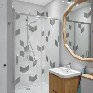Płytki z podłogi w kuchni i na przedpokoju zastosowano także w łazience, a ich kontynuacją są podobne wzory na ścianie pod prysznicem. Fot. JTgrupa