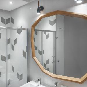 Małą przestrzeń zagospodarowano bardzo funkcjonalnie, zabudowując wnękę białymi drzwiami i stosując jasne kolory oraz drewniane dodatki w postaci szafki pod umywalkę i dużego lustra w asymetrycznym kształcie, które jednocześnie powiększa optycznie całe wnętrze. Fot. JTgrupa