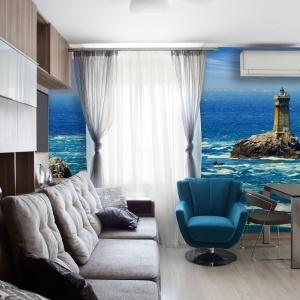Modna fototapeta z nadmorskim krajobrazem nadaje wyraz stonowanej kolorystyce salonu. Świetnie koresponduje też z turkusowym fotelem. Fot. Dekornik
