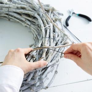 Krok 1: Kup lub zbierz kilka gałęzi, następnie pomaluj je na biało. Najlepiej użyć do tego zwykłego, białego sprayu. Następnie, zaginając gałązki, delikatnie uformuj je w wieniec, przewiązując sznurkiem dookoła w kilku miejscach.