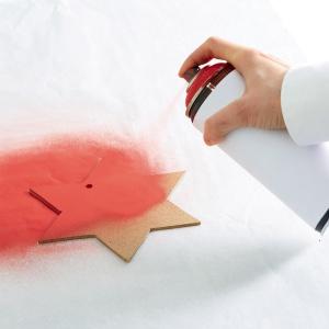 Krok 5: Spryskaj gwiazdę czerwonym sprayem z obu stron i poczekaj aż wyschnie. Możesz napisać na niej świąteczne życzenia. Następnie przepleć wstążkę przez wcześniej wywiercony w gwieździe otwór i przymocuj ją do wieńca.
