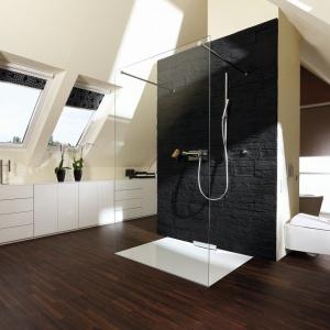 Pokój kąpielowy na poddaszu z powierzchnią prysznicową Xetis. Wokół komina zaaranżowano strefę prysznica, wanny oraz WC. Fot. Kaldewei