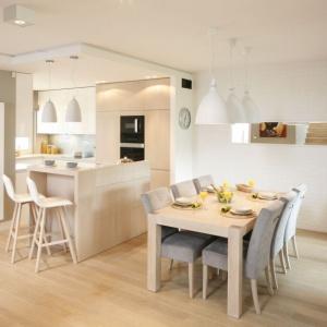 Piękne, jasne wybarwienie drewna doskonale pasuje do bieli. Taki duet stowrzył ciepłą, rodzinną kuchnię. Projekt: Małgorzata Galewska. Fot. Bartosz Jarosz