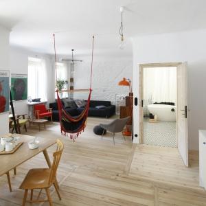 W obrębie jednego pomieszczenia domownicy mogą zrelaksować się na wygodnym szarym narożniku, zasiąść do dużego drewnianego stołu, a nawet pobujać na hamaku. Fot. Bartosz Jarosz