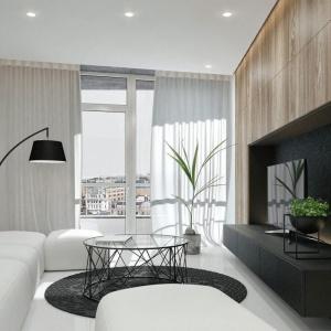 Strefa dzienna zaaranżowana w bieli i szlachetnym drewnie, z designerskimi smaczkami w postaci czarnej lampy czy modnego stolika kawowego. Fot. IDWhite