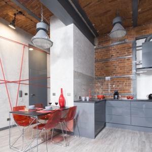 W tej kuchni ścianę nad blatem wykończono w dość nietypowy sposób. Połączono cegłę z betonem, który dodatkowo zabezpieczono szkłem. Projekt: Małgorzata Chabzda. Fot. Bartosz Jarosz