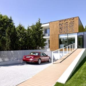 Bliźniaczy dom z lat 70-tych po przebudowie zyskał nowoczesny charakter. Niezwykła elewacja z paneli fornirowanych drewnem, w których wycięto ornamenty stanowi oryginalną ozdobę domu. Fot. Jeremi Buczkowski