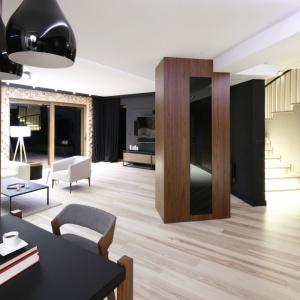 Gustownie urządzony przedpokój z elementami drewna i podświetlonymi schodami jest częściowo otwarty na salon. Projekt: Jan Sikora. Fot. Bartosz Jarosz