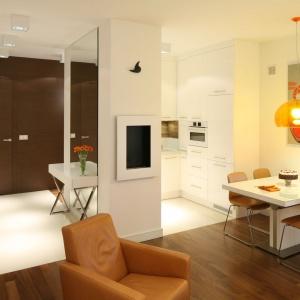 W niewielkim mieszkaniu też można interesująco zaprojektować strefę wejściową. Tu przedpokój otwarto na salon, zastosowano w nim drewno i lustro. Projekt: Małgorzata Galewska. Fot. Bartosz Jarosz