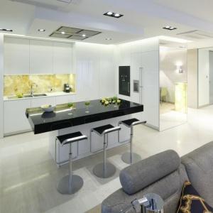 Tu przedpokój łączy się bezpośrednio z salonem i kuchnią. Całość optycznie powiększa lustro. Projekt: Anna Fodemska. Fot. Bartosz Jarosz