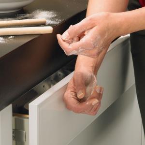 Dłonie ubrudzone w mące – żaden problem. Dzięki systemowi Easys nie ma obawy, że pobrudzimy meble. Wystarczy delikatnie nadgarstkiem nacisnąć front szuflady, a tak samodzielnie się otworzy. Fot. Hettich