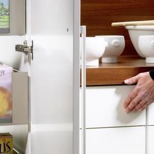 Lekkie dociśnięcie frontu powoduje, że tylna ściana szuflady uruchamia zamontowany z tyłu szafki czujnik. Ten natomiast wprowadza w ruch zasilany elektrycznie system wspomagający otwieranie szuflady. Fot. Hettich