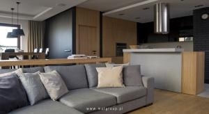 Wnętrze urządzone w stylu nowoczesnym z otwartą na siebie strefą dzienną i kuchnią.