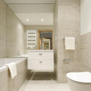 Łazienka utrzymana jest w jasnej kolorystyce. Ściany wykończone zostały płytkami. Projekt: Katarzyna Uszok. Fot. Bartosz Jarosz