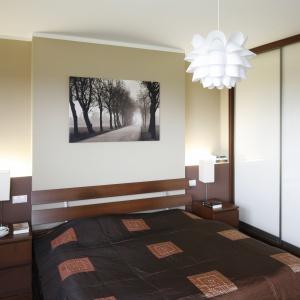 Ciepłą sypialnię z elementami drewna zdobi kwiatowa lampa sufitowa w białym kolorze. Kontrastują z nią lampki nocne o geometrycznym kształcie. Projekt: Piotr Stanisz.  Fot. Bartosz Jarosz