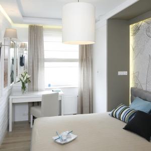 Nowoczesna sypialnia, z modną tapetą za łóżkiem i białą cegłą na przeciwległej ścianie wymagała odpowiedniego oświetlenia. Zastosowano tu białe, delikatne abażury w geometrycznych kształtach. Projekt: Małgorzata Mazur. Fot. Bartosz Jarosz