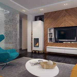 Bardzo elegancko zaaranżowano ściankę telewizyjną i strefę kominka. Biel połączona z naturalnym kolorem drewna nadaje wnętrzu wyjątkowo przytulnego charakteru. Fot. Archetyp