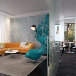 Salon to najbardziej reprezentacyjna część domu. Dzięki dużym przeszkleniom jest dobrze doświetlony i swobodnie otwiera się na ogród. Stosunkowo niewielką powierzchnię optycznie powiększono dzięki zastosowaniu transparentnych przesuwnych drzwi ze szkła, które delikatnie odseparowują pomieszczenie od kuchni i korytarza.  Fot. Archetyp