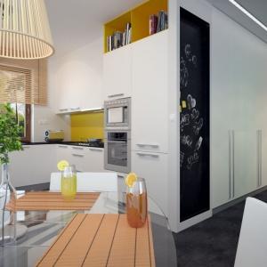 Kuchnia i jadalnia są dyskretnie oddzielone od salonu, ale dobrze z nim skomunikowane. Zastosowanie w kuchni dużego okna dodatkowo wizualnie powiększa pomieszczenie. Fot. Archetyp